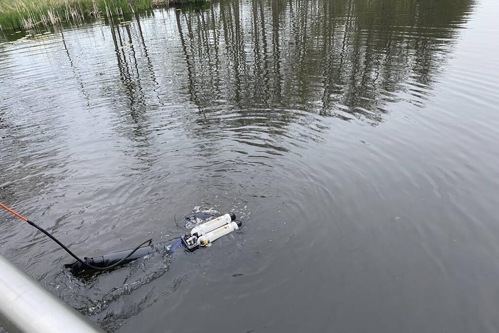 Brandweer duikt in het water gevallen telefoon op