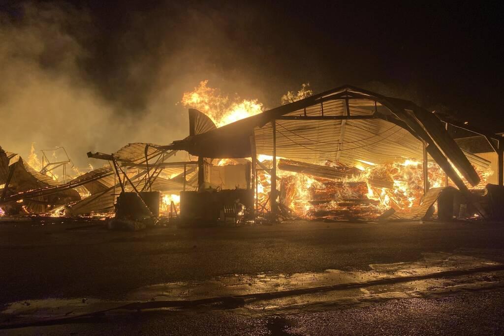 Brandweer bestrijdt grote uitslaande brand in twee loodsen