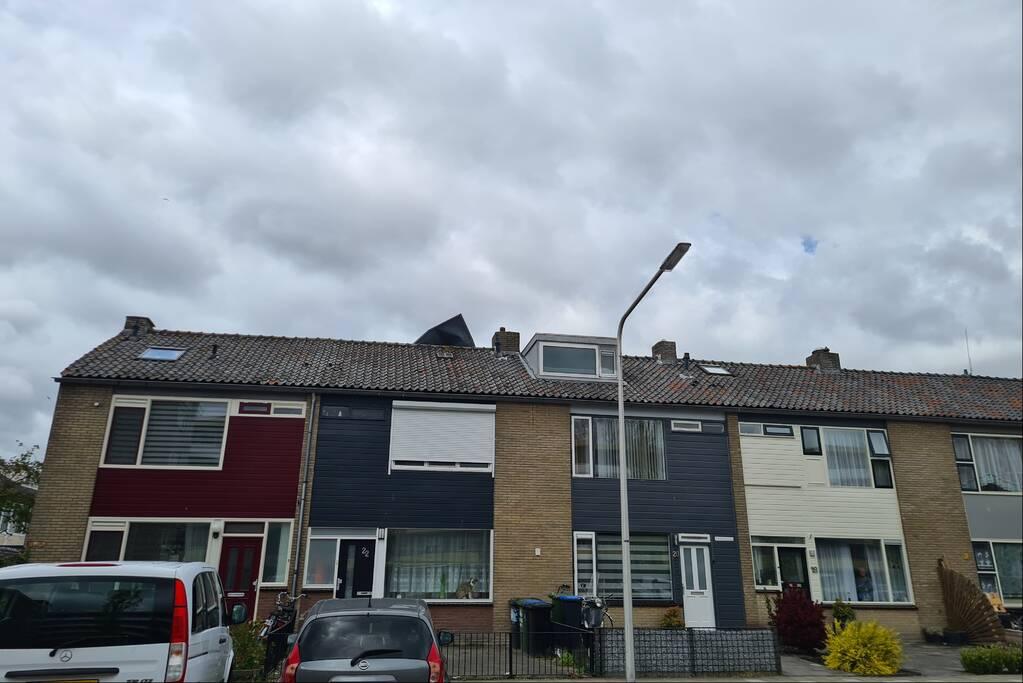 Dakbedekking waait van dakkapel van woning