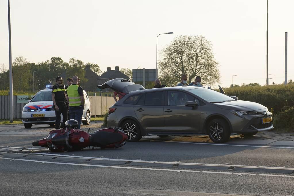 Personenauto en motor botsen op rotonde