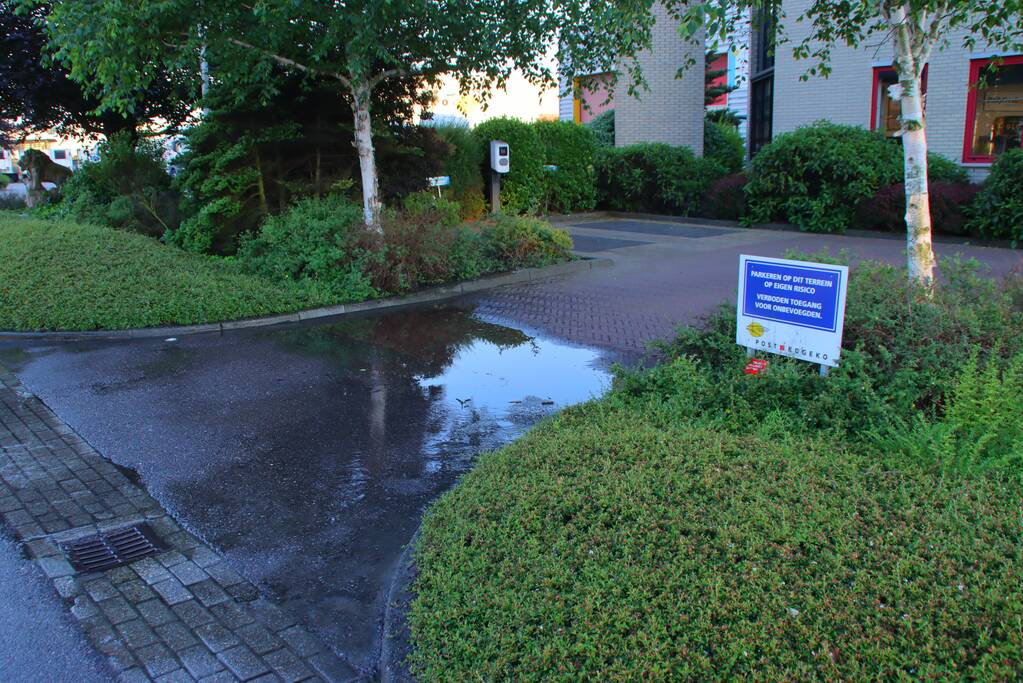 Waterlekkage op parkeerplaats van bedrijf