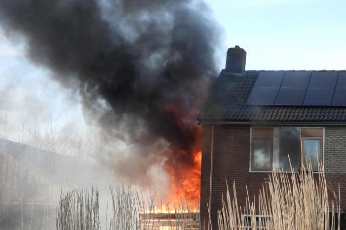 Uitslaande brand in schuur tegen woning aan