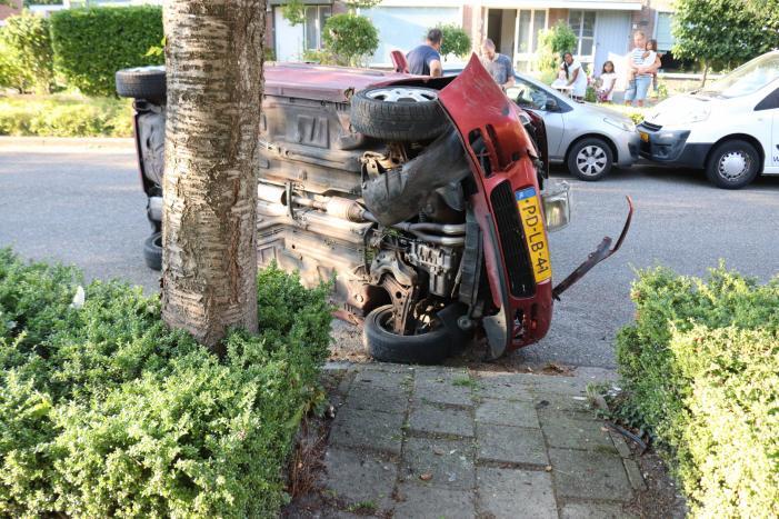 Bestuurder raakt onwel, botst op geparkeerde auto en belandt op zijn kant