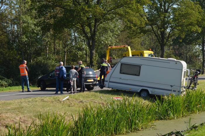 Auto met caravan raakt van de weg