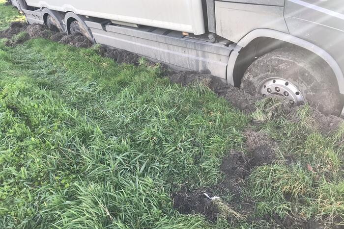 Vrachtwagen rijdt zich vast in berm langs snelweg