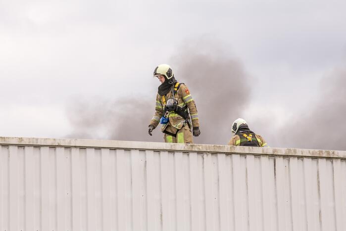 Vlammen slaan uit het dak bij meubelmakerij