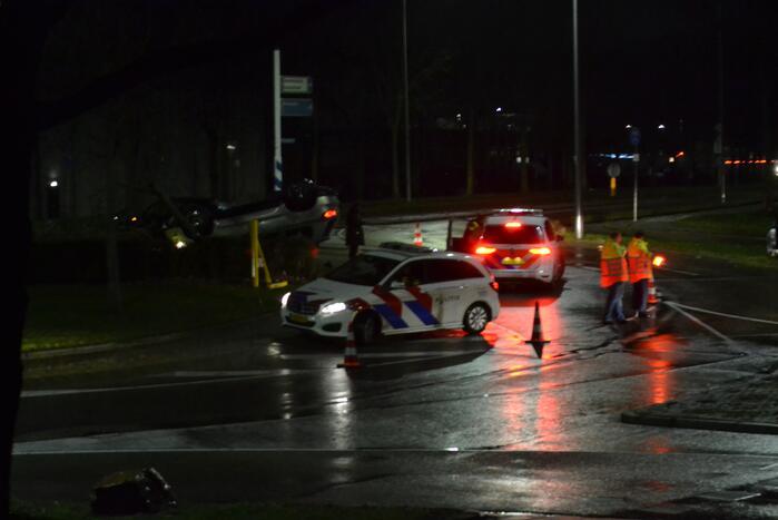 Auto belandt op de kop op rotonde