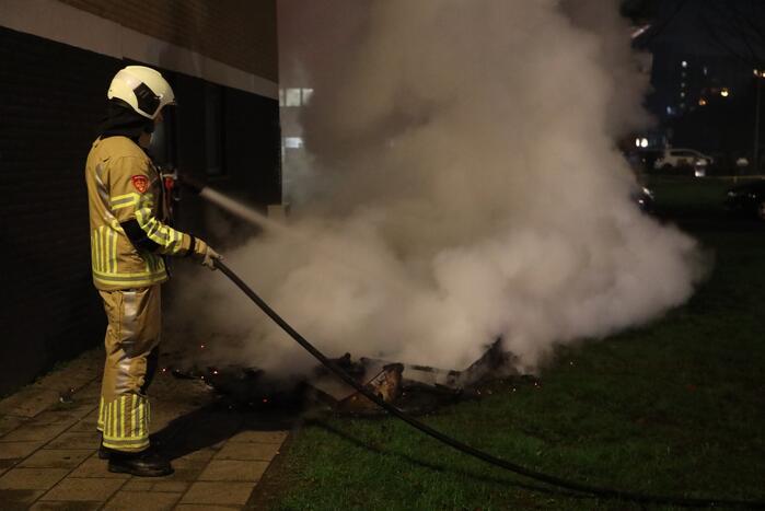 Hout en afval in brand tegen gevel