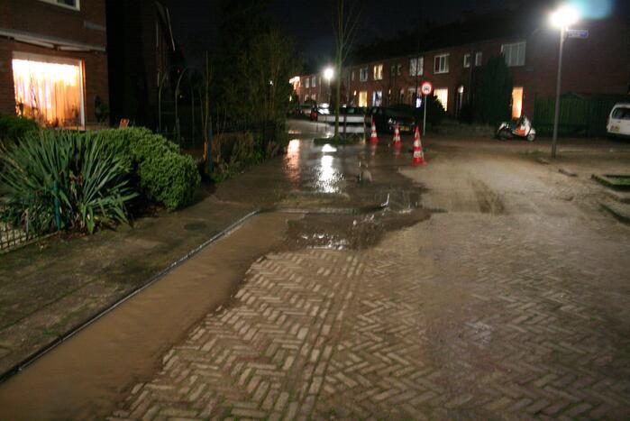 Straat onder water door gesprongen waterleiding