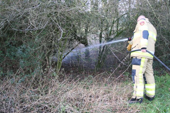 Brandweer blust autoband in bos