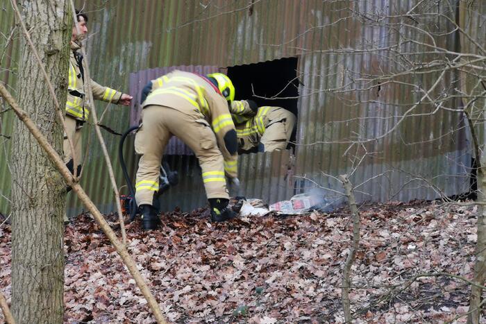 Brandweer blust brand in muur van golfplaten