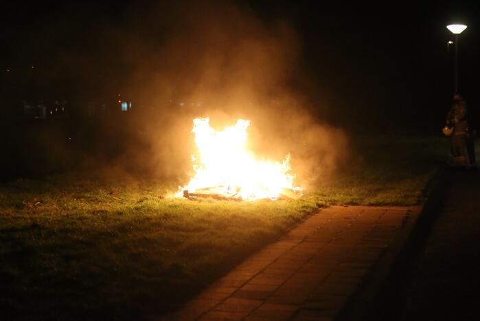 Brandweer blust brandende matras en pallets