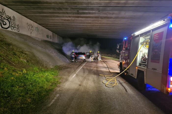 Auto vat vlam onder viaduct snelweg