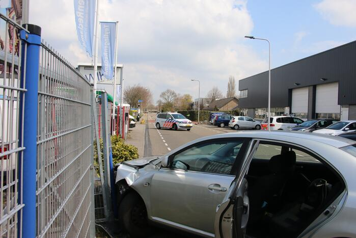 Auto knalt op hekwerk bedrijfspand