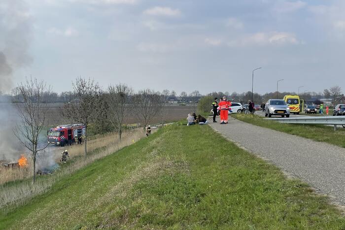Auto glijdt van dijk af na botsing en vliegt in brand