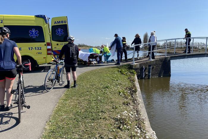 Vrouw kukelt met fiets van brug