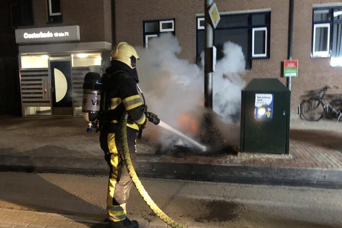 Houtstapel in brand naast container