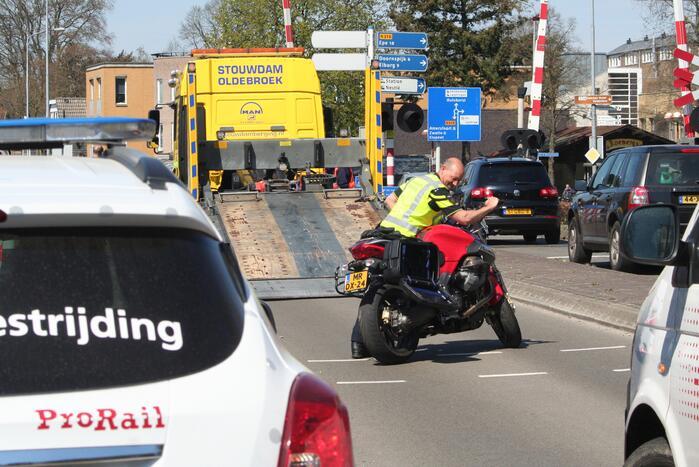 Motor heeft veel schade door botsing met personenauto en trein