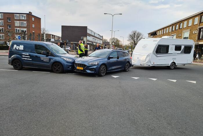 Personenauto met caravan in botsing met bestelbus