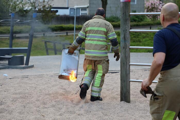 Brandweer blust brand in afvalcontainer