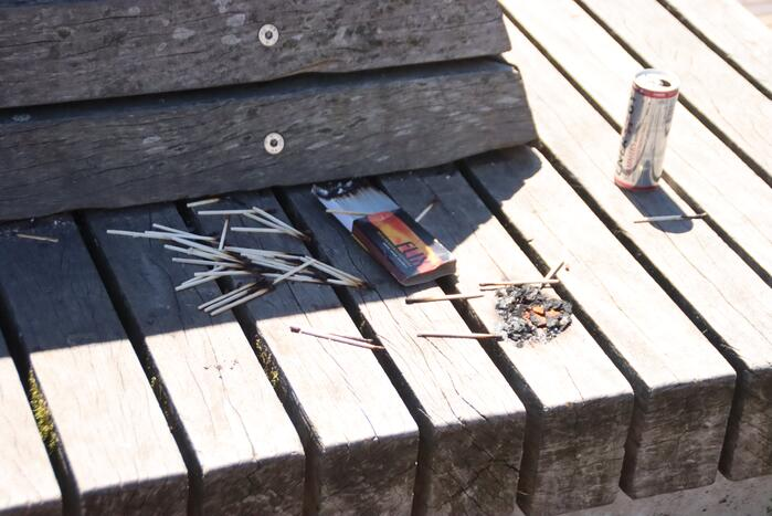 Brandgesticht op houten bank