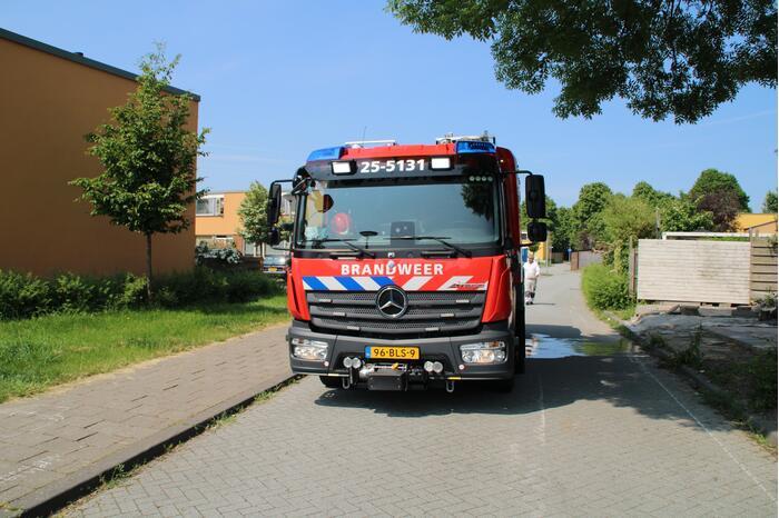 Brandweer blust in brand staande schutting