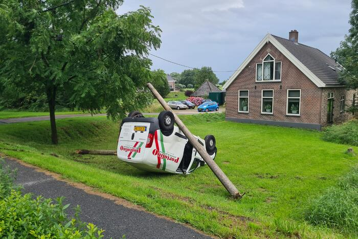 Bezorgauto slaat over de kop en ramt stroommast