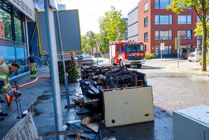 Bouwcontainer met bouwafval vat vlam