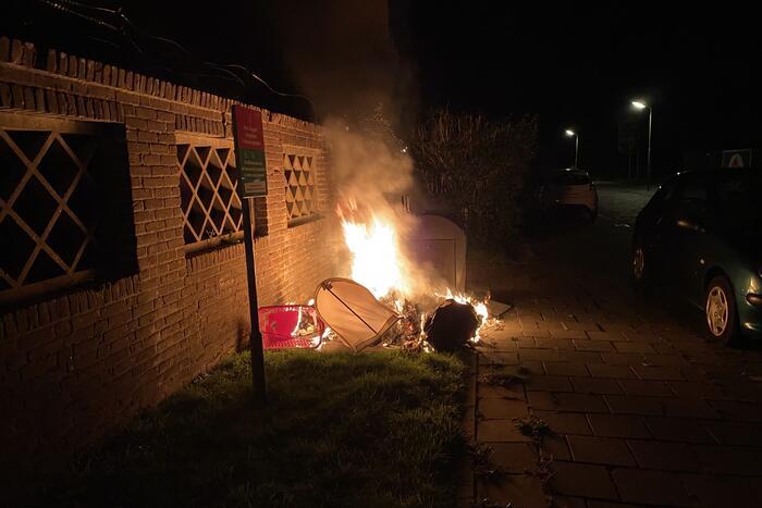 Brandweer blust brand bij container