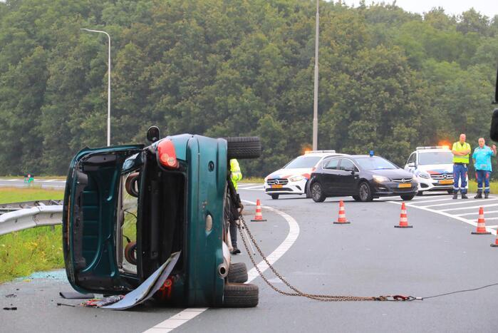Auto glijdt over vangrail heen en belandt op zijn kop