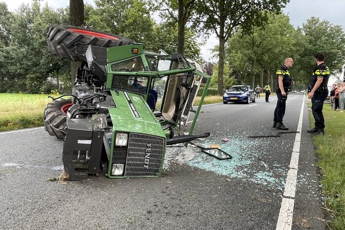 Tractor over de kop na botsing met boom