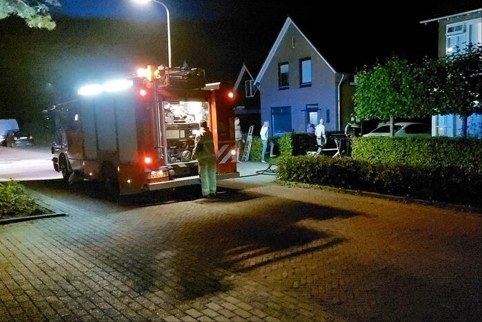 Brandweer blust brand aan achterzijde van woning