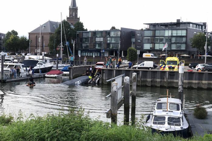 Omgeslagen boot wordt opgetakeld in jachthaven
