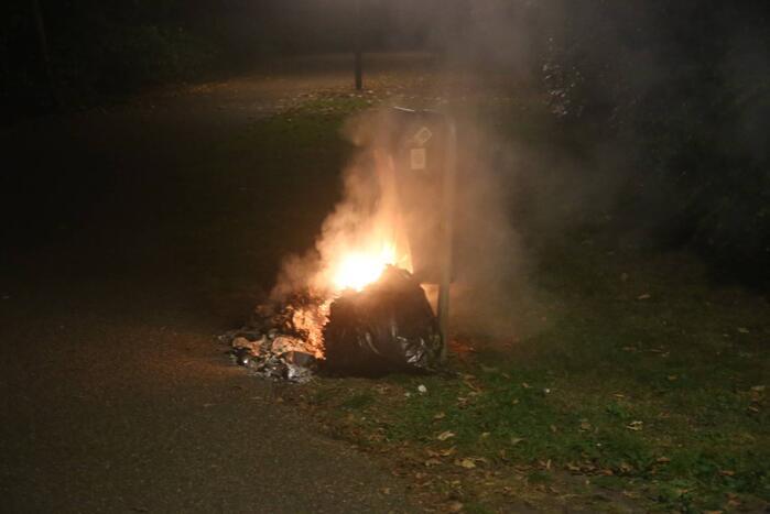 Brandweer blust brand bij prullenbak