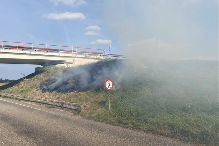 Berm talud naast snelweg vat vlam